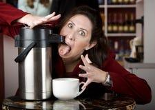 Café de consumición de la mujer directamente de un dispensador imagen de archivo