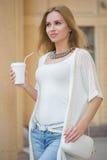 Café de consumición de la mujer elegante a entrar en una ciudad Fotografía de archivo