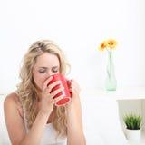 Café de consumición de la mujer en cama Fotografía de archivo libre de regalías