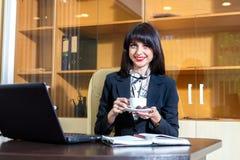 Café de consumición de la mujer hermosa en una tabla Fotos de archivo libres de regalías