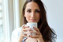 Café de consumición de la mujer hermosa por la mañana cerca de la ventana Foto de archivo libre de regalías