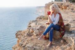 Café de consumición de la mujer hermosa que se sienta en la orilla rocosa foto de archivo libre de regalías