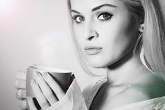 Café de consumición de la mujer hermosa Taza de té Bebida caliente Retrato monocromático imagenes de archivo