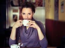 Café de consumición de la mujer joven Fotografía de archivo libre de regalías