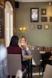 Café de consumición de la mujer joven con el amigo femenino Fotos de archivo libres de regalías