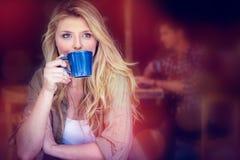 Café de consumición de la mujer joven con el hombre que se sienta en fondo Fotos de archivo libres de regalías