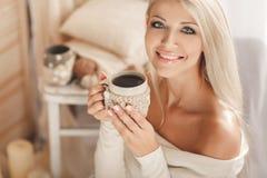 Café de consumición de la mujer joven en casa en su sitio Imagenes de archivo