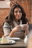 Café de consumición de la mujer joven en un café Fotografía de archivo