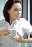 Café de consumición de la mujer joven por la mañana Imagen de archivo libre de regalías