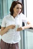Café de consumición de la mujer joven por la mañana Imagenes de archivo