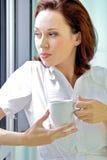 Café de consumición de la mujer joven por la mañana Foto de archivo