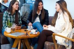 Café de consumición de la mujer joven tres y discurso en la tienda del café Imagenes de archivo
