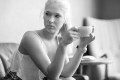 Café de consumición de la mujer joven y bonita en el café Foto de archivo