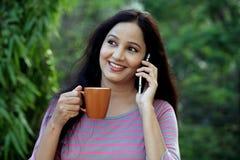 Café de consumición de la mujer joven y el hablar en el teléfono móvil Imagen de archivo