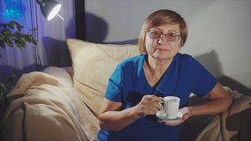 Café de consumición de la mujer mayor pensativa de la taza blanca almacen de metraje de vídeo
