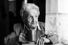 Café de consumición de la mujer mayor, retrato blanco y negro Sonrisa imágenes de archivo libres de regalías