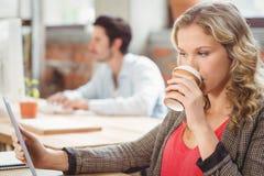 Café de consumición de la mujer mientras que mira la tableta digital Fotografía de archivo