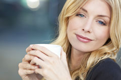 Café de consumición de la mujer rubia hermosa Foto de archivo libre de regalías