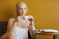 Café de consumición de la mujer rubia joven en el café Fotos de archivo