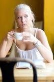 Café de consumición de la mujer rubia joven en el café Imágenes de archivo libres de regalías