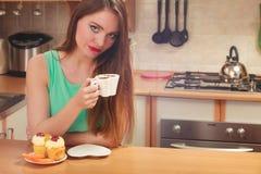 Café de consumición de la mujer y consumición de la torta deliciosa Fotografía de archivo