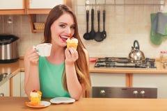 Café de consumición de la mujer y consumición de la torta deliciosa Imagenes de archivo