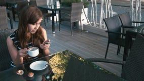 Café de consumición de la mujer y mirada de smartphone almacen de video