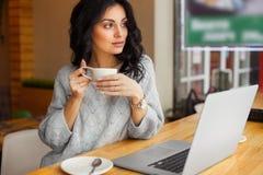 Café de consumición de la mujer y mirada hacia fuera de la ventana Imagen de archivo