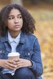Café de consumición de la raza mixta de la mujer afroamericana triste del adolescente Foto de archivo libre de regalías