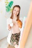 Café de consumición de la señora caucásica joven alegre que come el cruasán Imagenes de archivo