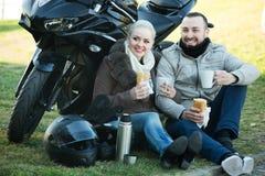 Café de consumición de los pares cerca de la motocicleta Fotografía de archivo