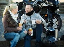 Café de consumición de los pares cerca de la motocicleta Imagen de archivo libre de regalías