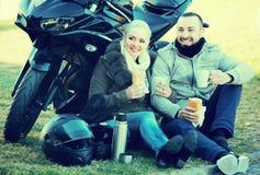 Café de consumición de los pares cerca de la motocicleta Imagenes de archivo