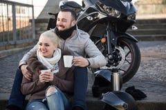 Café de consumición de los pares cerca de la motocicleta Fotografía de archivo libre de regalías