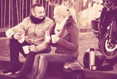 Café de consumición de los pares cerca de la motocicleta Imágenes de archivo libres de regalías