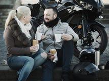 Café de consumición de los pares cerca de la motocicleta Fotos de archivo