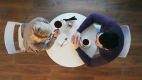 Café de consumición de los pares jovenes felices y el hablar en cafetería almacen de video