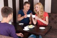 Café de consumición de tres personas jovenes Foto de archivo libre de regalías