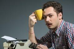 Café de consumición del autor en la máquina de escribir Fotos de archivo libres de regalías