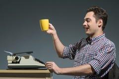 Café de consumición del autor en la máquina de escribir Imágenes de archivo libres de regalías