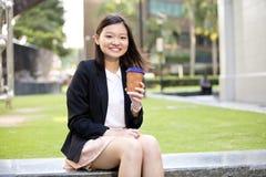 Café de consumición del ejecutivo de sexo femenino asiático joven y usar la PC del ordenador portátil Fotos de archivo