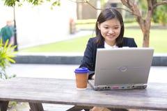 Café de consumición del ejecutivo de sexo femenino asiático joven y usar la PC del ordenador portátil Fotos de archivo libres de regalías