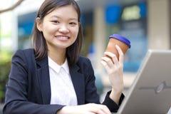 Café de consumición del ejecutivo de sexo femenino asiático joven y usar la PC del ordenador portátil Imagen de archivo