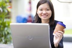 Café de consumición del ejecutivo de sexo femenino asiático joven y usar la PC del ordenador portátil Imagenes de archivo