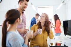 Café de consumición del equipo creativo feliz en la oficina Imagen de archivo