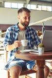 Café de consumición del hombre adulto joven alegre Fotografía de archivo libre de regalías