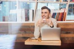 Café de consumición del hombre alegre mientras que se sienta en café Fotografía de archivo