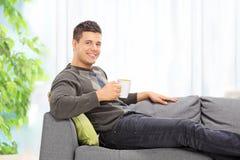 Café de consumición del hombre asentado en el sofá en casa Fotografía de archivo libre de regalías