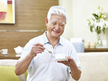 Café de consumición del hombre asiático mayor Imagenes de archivo