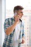 Café de consumición del hombre atractivo y el hablar en el teléfono móvil Foto de archivo